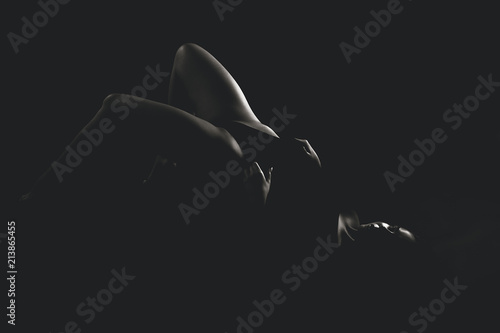 Photographie  Sexy young lady in black bodysuit, posing in dark studio