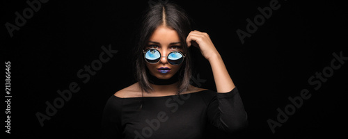 Portrait of cool crazy brunette fashionable girl in sunglasses, casual hairdo on black background Wallpaper Mural
