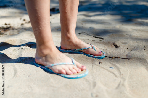 5af60e4f5f657e Feet Girl with a neat pedicure in women s stylish beach flip-flops aqua on  the beach background. Two sandals on the sand near the sea.