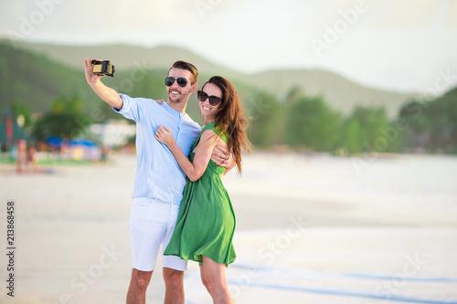 Fotografia Happy couple taking a photo on white beach on honeymoon holidays
