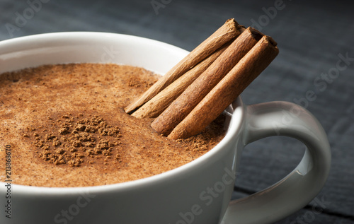 Close up white cup of salep milky hot drink of Turkey with cinnamon powder healthy spice on black wooden background