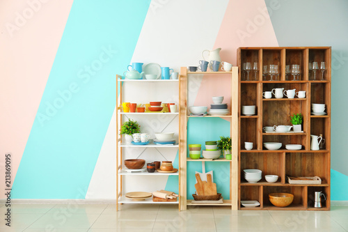 Kitchen shelving with dishes on color wall background Canvas Print