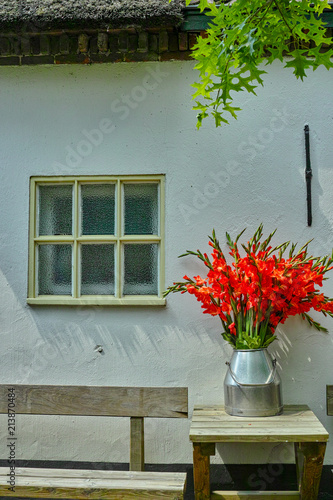 Big Bouquet Of Red Gladiolus Flowers In Old Milk Can On Table