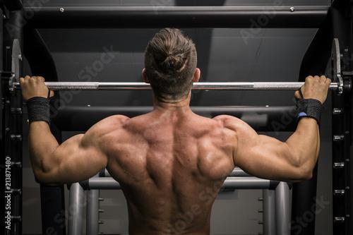 Fotografie, Obraz  Hombre fuerte con grandes músculos haciendo dominadas en el gimnasio de espaldas