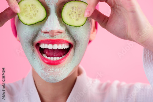 Fotografie, Obraz  Close up portrait of woman with facial cosmetical mask and cucumber slice on eyes