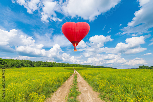 Tuinposter Helicopter Red hot air balloon in the shape of a heart.