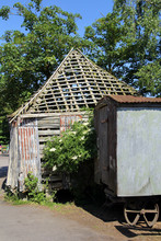 A Dilapidated Falling Down Old Farmyard Building With An Old Iron Wheeled Farm Wagon, On A Sunny Day With Trees