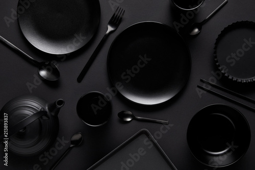 Photo  top view of black teapot, plates, bowl, cups, tray, spoons, chopsticks, fork and