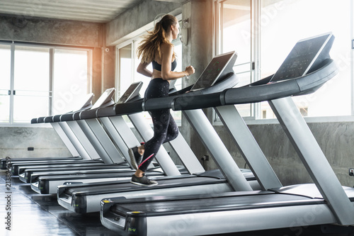 Fotografia Cute young woman exercising on  treadmill at a gym