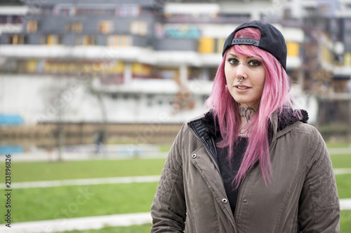 Fotografie, Obraz  young alternative woman with pink hair standing in front of run-down housing est