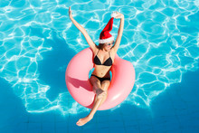 Beautiful Crazy Woman In Santa Claus Hat Relaxing On Inflatable Ring In Blue Swimming Pool