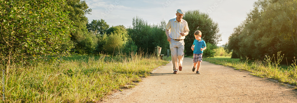 Fototapeta Front view of senior man with hat and happy child running on a nature path. Two different generations concept.