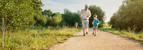 Fotografia  Front view of senior man with hat and happy child running on a nature path