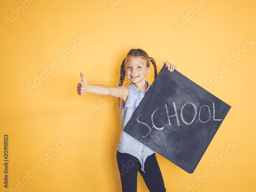 Fotografie, Obraz  blond girl is standing in front of yellow, orange background and is holding a bl