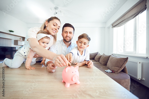 Valokuva A smiling family saves money with a piggy bank