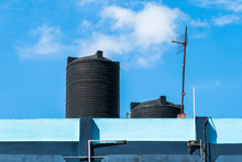 Water Tank On The Roof Over Blue Sky