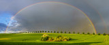 Fototapeta Tęcza - double, beautiful, multi-colored rainbow after passing a spring downpour over a green field