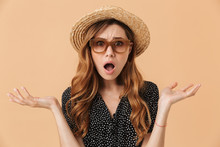Portrait Of Frustrated Perplexed Woman 20s Wearing Straw Hat And Sunglasses Throwing Arms Aside, Isolated Over Beige Background
