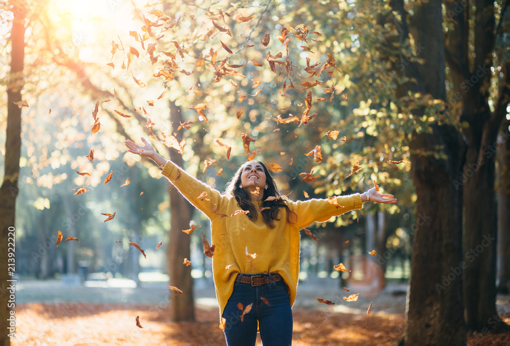 Fototapety, obrazy: Casual joyful woman having fun throwing leaves in autumn at city park.