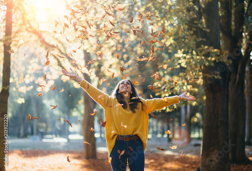 Fototapeta Casual joyful woman having fun throwing leaves in autumn at city park. obraz