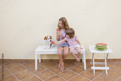 Fotografiet  Two beautiful sister kids eating a watermelon ice cream with their cute dog