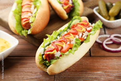 Hot dogs with ketchup, mustard and vegetables on wooden table Canvas Print