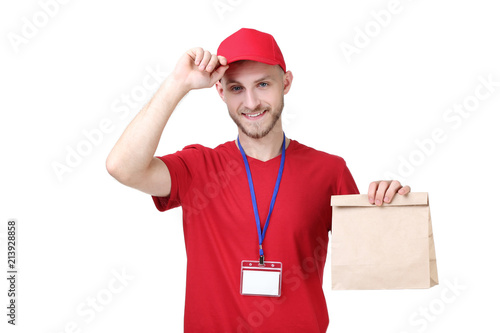 Fotografie, Obraz  Delivery man in red uniform with paper bag on white background