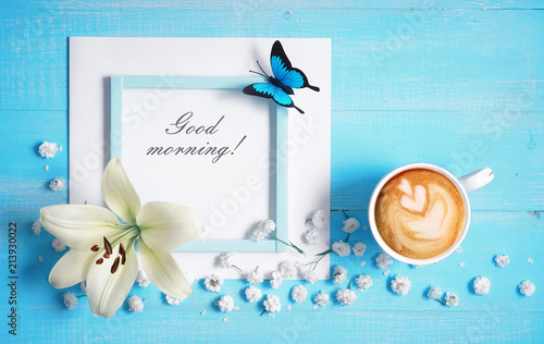 Valokuvatapetti Cup of cappuccino coffee, lily flower, butterfly and  inscription Good morning on blue wooden background