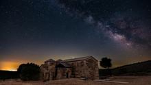 Night View Of Santa Lucia Del Trampal In Alcuéscar (Spain) With Milky Way Galaxia