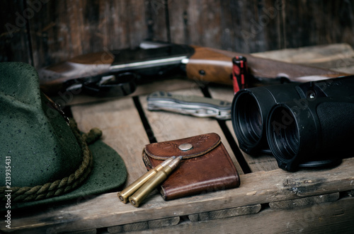Poster Jacht Professional hunters equipment for hunting. Detail on the ammunition. Wooden black background with rifle, hat, and other equipment for hunting.