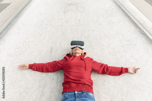 Senior woman lying on the ground wearing VR glasses