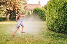Child Playing With Garden Spri...