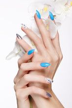 Beautiful Summer Blue Manicure On Female Hand With Flowers. Close-up. Picture Taken In The Studio