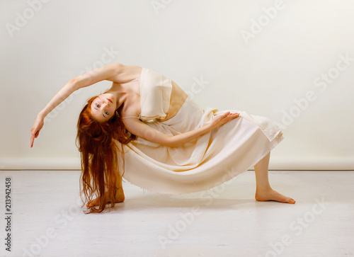 Young redhead woman does stretching and yoga poses, dancing contemporary dance, posing in studio, . Copy space