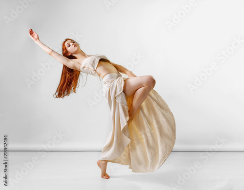 Dancer posing in studio. Young and beautiful redhead girl in a beige long skirt and top dances and poses in studio. Copy space Wall mural