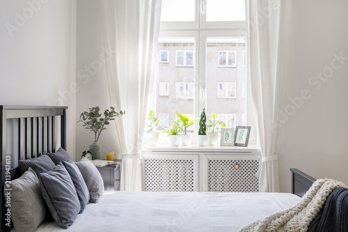 Obraz Knit blanket and pillows on bed in white hotel bedroom interior with drapes at window. Real photo - fototapety do salonu