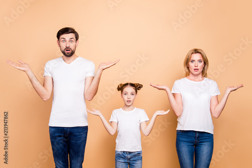 Obraz Portrait of young family bieng confused, bearded father, blonde mother and their little daughter wearing jeans and T-shirts, showing uncertain gesture with their hands - fototapety do salonu