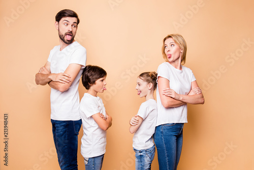 Fotografía  Portrait of attractive beautiful family, bearded father, blonde mother standing back to back with their little children wearing jeans and white T-shirts, with crossed arms