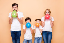 Young Family, Bearded Father, Blonde Mother, Boy And Girl Wearing Blue Jeans And White T-shirts, Blowing Air Balls Green Beige Red Blue