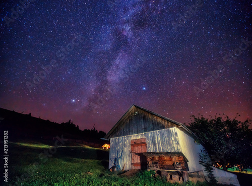 View at the starry sky and old house on mountain slope.