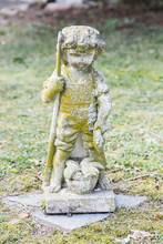 Sculpture Of Boy Holding Fish And Fishing Rod In His Hand