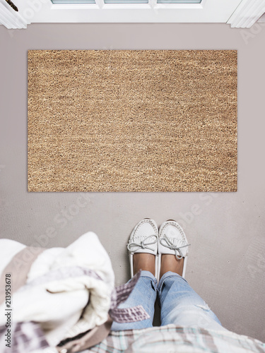 Blank doormat before the door in the hall. Mat on gray floor, girl in white shoes. Welcome home, product Mockup