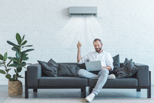 Handsome Man Turning On Air Conditioner With Remote Control While Using Laptop On Sofa At Home