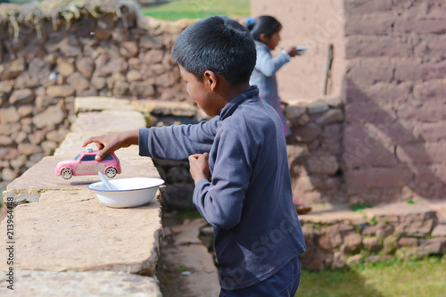 Fotografie, Obraz  Native american little boy playing with old plastic toy car in the countryside