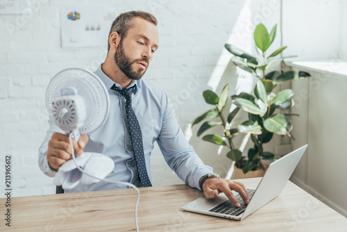 businessman cooling himself with electric fan while using laptop in office - 213965612
