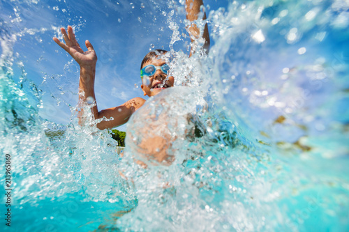 Happy boy playing and splashing in swimming pool Fototapeta