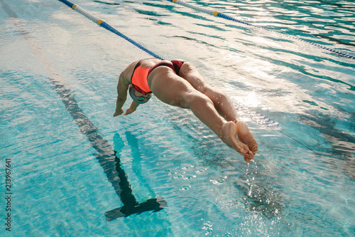 Fotografia Female swimmer diving into indoor sports swimming pool