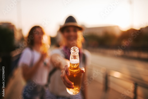 Girl offering a drink or toasting Fototapet