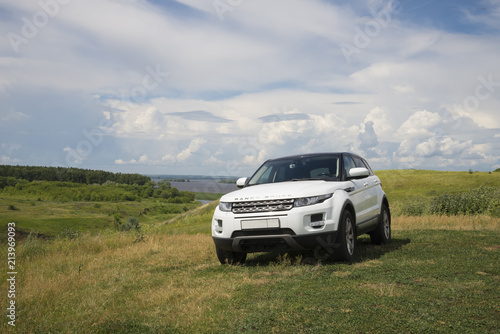 Fotografie, Obraz Car Land Rover Range Rover is standing at green grass at summer day near the city of Chistopol, Tatarstan, Russia