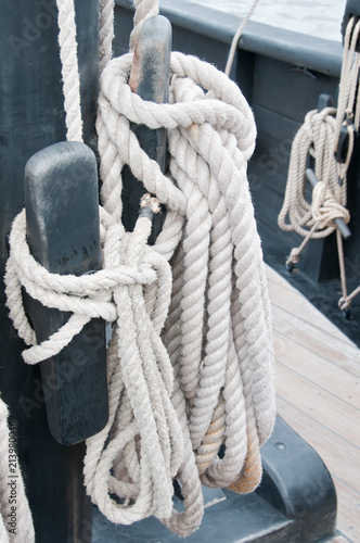 Fotografie, Obraz  Detail of a halyard coiled neatly and secured on a cleat on the authentic replica of the Nina, one of Columbus's sailing ship